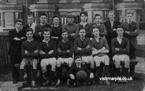 A football team posing with Barnsfold Road, Hawk Green in the background.
