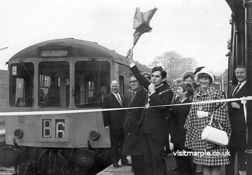 Monty Burton waves the flag at the official reopening of Marple Station on 28 October 1970.